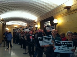 Crowd with MN against photo voter ID signs