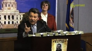Representative Tom Rukavina behind a wall of $1,000 in reward money