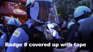 Chicago cop with tape over badge during NATO protests